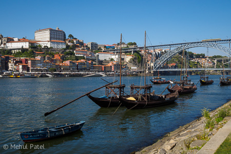 Old style wooden boats (Rabelos) moored on the river Douro by Cais de Gaia overlooking the the historic part of Porto, Ribeira and the Ponte Luis I, Portugal. Rabelos are typical vessels of the Douro River which once traditionally carried barrels of Port wine from where the vineyards are located to Vila Nova de Gaia - Porto, where the wine was stored and then distributed.